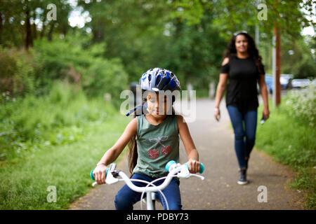 Madre Hija viendo bicicleta sobre la ruta Imagen De Stock