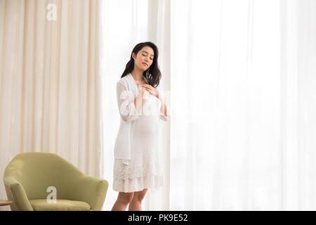 Alegre mujer embarazada de pie en el salón Imagen De Stock