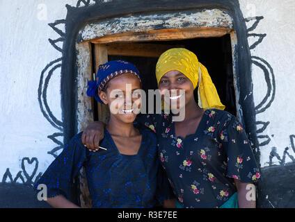 Raya tribu gilrs sonriente a la entrada de un decorado hut, región de Afar, en Etiopía, Chifra Imagen De Stock