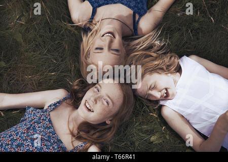 Retrato feliz hermanas sentar en la hierba Imagen De Stock