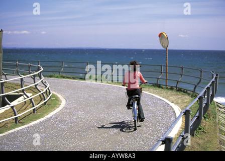 Mujer en una bicicleta por el mar Imagen De Stock
