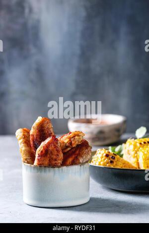 Barbacoa, alitas de pollo picante servido en cuenco de cerámica con salsa roja, asados de maíz dulce y perejil bundle en el cuadro azul claro. Imagen De Stock