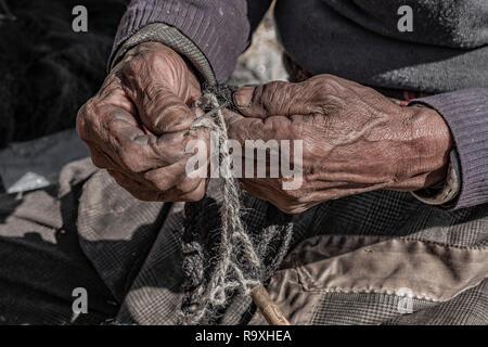 Nepal artesano con ensuciándose las manos trenzando una cuerda de yak, piel de vaca. Imagen De Stock