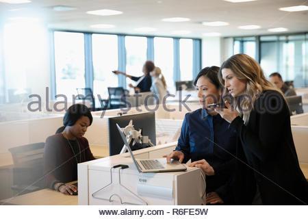 Empresarias mediante teléfono inteligente y ordenador portátil en la oficina Imagen De Stock