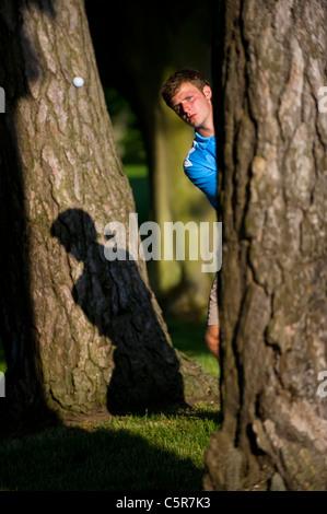 Un golfista jugando un disparo de los árboles se centró en la bola. Imagen De Stock