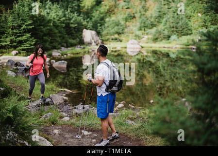 Par de senderismo a lo largo de lago en el bosque Imagen De Stock