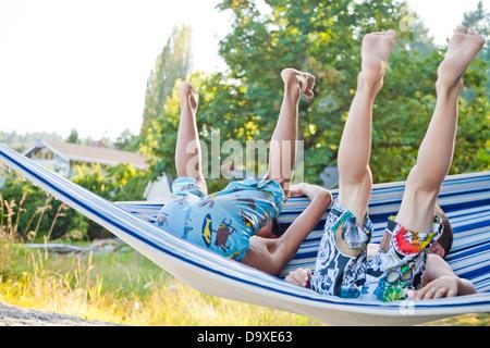 Niños jugando en una hamaca en la playa Imagen De Stock