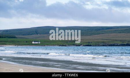 Vista de la casa blanca y el mar en Laggan Bahía de Islay en el interior de islas Hébridas, Escocia, Reino Unido Imagen De Stock