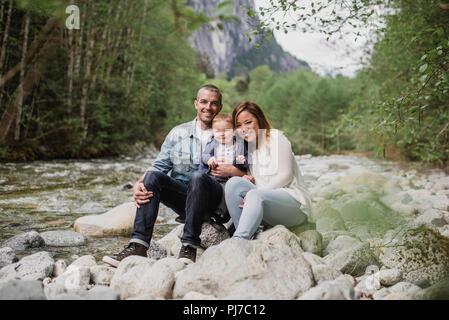 Retrato de los padres y su hijo sentados en las rocas en el Riverside Imagen De Stock
