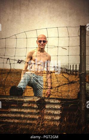 Joven hombre enojado con cabeza calva de pie cerca de la valla de alambre Imagen De Stock