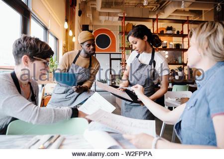 Servidores discutiendo menú en un restaurante Imagen De Stock