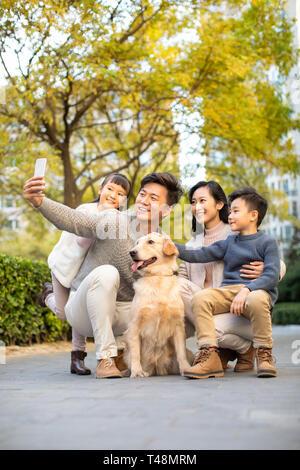 Feliz familia joven teniendo un selfie con su perro Imagen De Stock