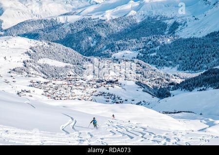 Hermosas montañas nevadas con Arosa village. Volver país esquiador en primer plano dejan sus huellas en la nieve profunda. Imagen De Stock