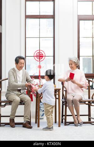 Los abuelos dando bolsas rojas nieto Imagen De Stock