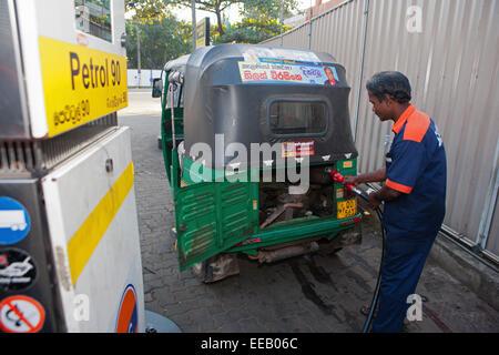 Gasolinera llenando el rickshaw con gasolina. Imagen De Stock
