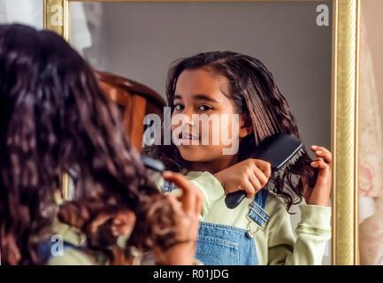 Jóvenes de 7-8 años de edad, niña cepillarse el cabello mientras se mira en el espejo. Preparándose para la escuela. © Myrleen Pearson .......Ferguson Cate Imagen De Stock