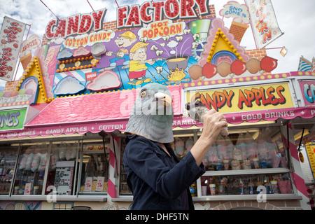 Persona llevaba una máscara de paloma posee una pata de pavo en State Fair. Imagen De Stock