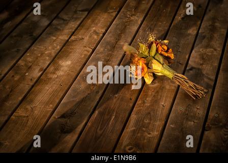 Un viejo y decoloración ramo de secado descartado flowerd reside en un piso de madera. Imagen De Stock