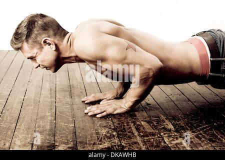 Mitad hombre adulto haciendo flexiones sobre un piso de madera Imagen De Stock