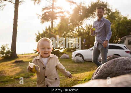 Baby Boy (18-23 meses) la celebración de banana Imagen De Stock