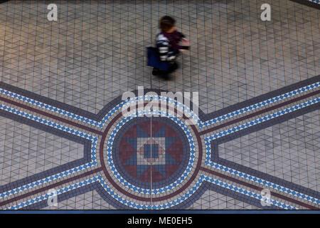Persona caminando en el piso de baldosas de mosaico en el edificio Queen Victoria en el Distrito Central de Negocios de Sydney, Australia Imagen De Stock
