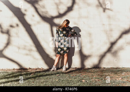 Mujer joven posando contra la pared con sombra de árboles Imagen De Stock