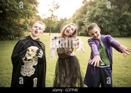 Tres niños vestidos de traje para la noche de Halloween. Imagen De Stock