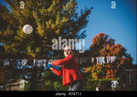 Chica preparándose para golpear la bola de béisbol en el jardín Imagen De Stock