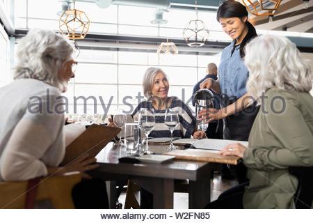 Camarera sirviendo a mujeres mayores amigos en restaurante. Imagen De Stock