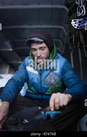 Macho joven escalador preparar equipos de escalada en autocaravana Imagen De Stock