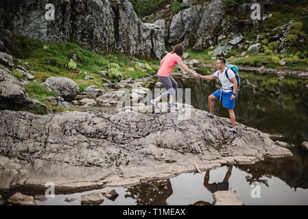 Excursión pareja sobre rocas, perro de montaña, BC, Canadá Imagen De Stock