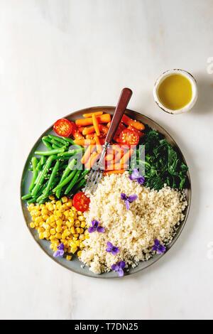 Cuscús con verduras cocidas con piel de bebé zanahorias, judías verdes, maíz dulce, las espinacas servido en placa de cerámica con tomate, sésamo y flores comestibles. Ve Imagen De Stock
