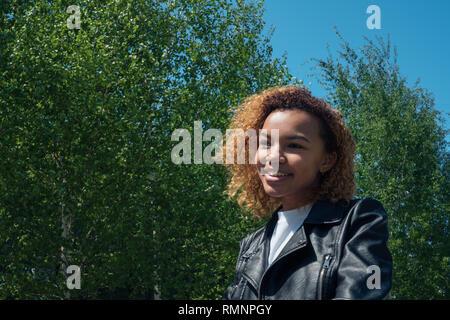 Linda muchacha africana cuidadosamente mira lejos con una hermosa sonrisa en el muelle exterior Imagen De Stock