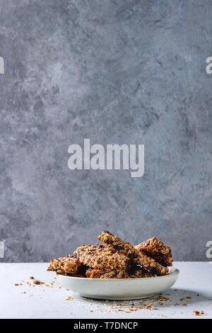 Energía casera avena barras de granola con frutos secos y nueces enteras y roto en placa de cerámica en el cuadro gris. Refrigerio saludable. Imagen De Stock