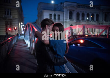 Par de pie sobre un puente en la noche abrazando, Bosnia y Herzegovina Imagen De Stock