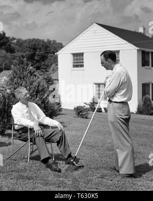 1950 dos hombres en el patio de vecinos hablando uno sentado otros con rastrillo permanente - s5808 HAR001 HARS menores hijos COMUNICACIÓN LIFESTYLE ELDER CASAS RAKE vida doméstica ASENTADO ESPACIO COPIA AMISTAD PERSONAS DE LONGITUD COMPLETA hombres altos edificios residenciales hombre adulto SENIOR PADRES B&W VECINOS OLDSTERS DODO PAPÁS EXTERIOR PADRE E HIJO en hogares de ancianos conexión residencia viejos y jóvenes menores de cooperación elegante silla de jardín Mediados de-adulto hombre adulto medio COMPAÑERISMO EN BLANCO Y NEGRO la etnia CAUCÁSICA HAR001 ANTICUADO Imagen De Stock