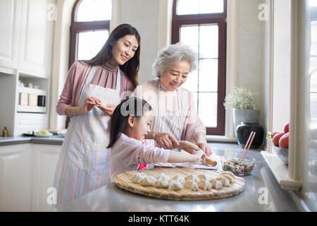 Familia alegre haciendo dumplings en la cocina Imagen De Stock