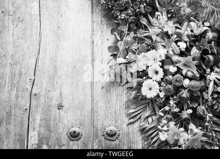 Ofrenda floral en la puerta de madera desgastada con copia espacio en blanco y negro impresionante Imagen De Stock