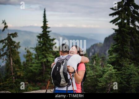 Pareja feliz, abrazando el senderismo en la montaña, la Montaña del Perro, BC, Canadá Imagen De Stock