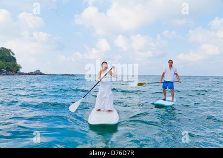 Viste al hombre y a la mujer de equitación boards paddle Imagen De Stock