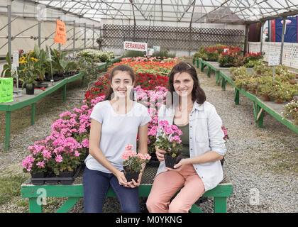 Madre e hija del Cáucaso sonriente sosteniendo flores en vivero Imagen De Stock