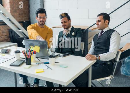 Los científicos chicos de diferentes nacionalidades están estudiando activamente el proyecto en Internet. Los empresarios trabajan en un portátil. Imagen De Stock