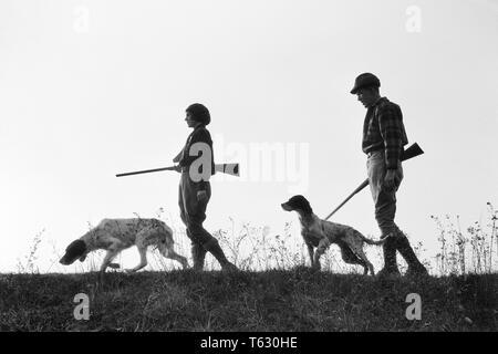 1920 1930 silueta anónima al hombre y a la mujer los cazadores que portan armas, cada uno con un perro de caza - S2541A HAR001 HARS SILUETAS DE OCIO Y RECREO CANINOS POOCH Conexión anónima COOPERACIÓN CANINA ARMA ARMAS DE FUEGO CAZADORES mamífero adulto medio hombre adulto medio Mediados de-MUJER ADULTA COMPAÑERISMO EN BLANCO Y NEGRO HAR001 ANTICUADO Imagen De Stock