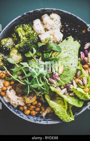 Almuerzo o cena saludable en casa. Superbowl vegano o Buda bowl con hummus, ensaladas frescas, verduras, frijoles, cuscús y aguacate en tabla, vista superior Imagen De Stock