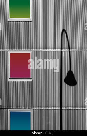 Una lámpara curvada distintivamente sombra en una pared con tres ventanas. Imagen De Stock