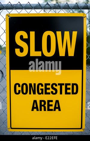 Un signo de advertencia de color amarillo de lectura: lento - zona congestionada, colgando de un cercado de cadenas Imagen De Stock