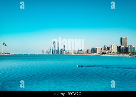 Skyline de Abu Dhabi costanera con botes de pesca cruzando la escena. La esquina izquierda de la foto muestra una enorme bandera de los emiratos árabes. Imagen De Stock