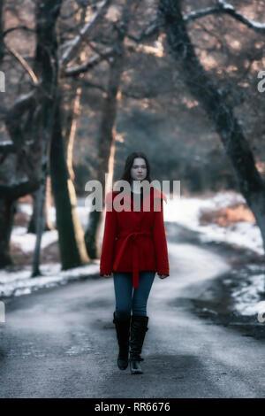 Una mujer joven con una chaqueta roja caminando por una calle pequeña en un bosque invernal con nieve Imagen De Stock