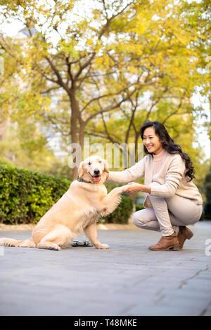 Feliz joven sacude la pata del perro Imagen De Stock