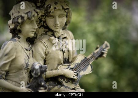 Antigua estatua de una joven pareja de amor - chico y chica, con boy tocando instrumentos musicales. Imagen De Stock